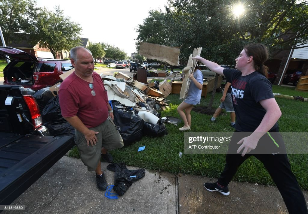 Members of the Olson family remove debris and damaged items from their father's home in the Twin Oaks Estate after Hurricane Harvey caused widespread flooding in Houston, Texas on August 31, 2017. In Houston, America's fourth-largest city, some of the 2.3 million residents got relief as the raging waters receded. But in several other towns in the Lone Star State doused by days of torrential rains since Harvey smashed into the US Gulf Coast almost a week ago as a Category Four hurricane, the situation was dire. RALSTON