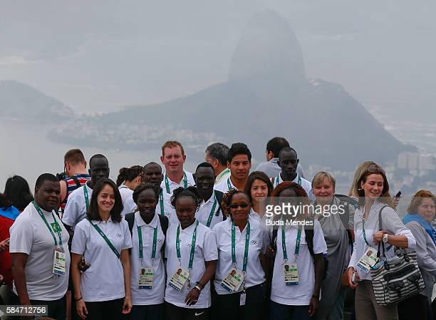 Members of the Olympic refugee team pose at the statue of Christ the Redeemer with the Sugar Loaf mountain behind them on July 30 2016 in Rio de...