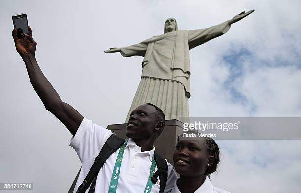 Members of the Olympic refugee team pose for selfies in front of Christ the Redeemer on July 30 2016 in Rio de Janeiro Brazil A group of 10 athletes...