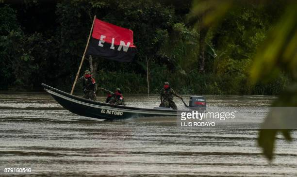 Members of the Omar Gomez Western War Front of the National Liberation Army guerrilla patrol the San Juan river near their camp in the department of...