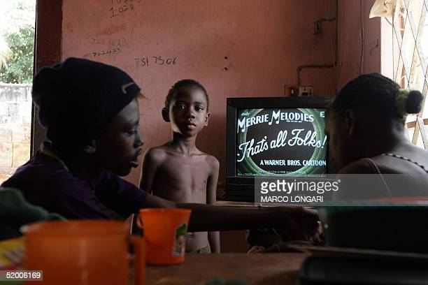 Members of the Onesime family watch television in the house they share with 26 other family members in Port Louis Mauritius 17 January 2005 The...
