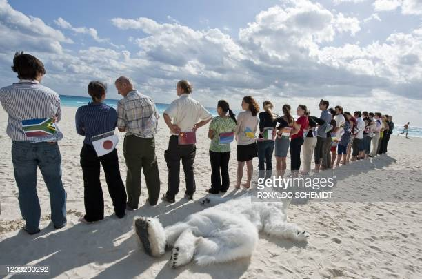 Members of the ONG Sierra Club demonstrate against the countries who according to them are avoiding the climate change issue, in a beach in Cancun on...