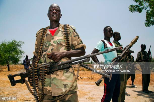 TOPSHOT Members of the opposition troops hold weapons near their base in Thonyor in Leer county on April 11 2017 At least 16 civilians were killed in...