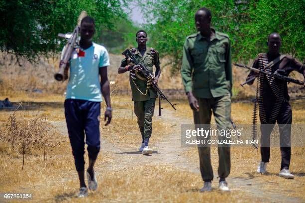 Members of the opposition troops hold weapons near their base in Thonyor in Leer county on April 11 2017 At least 16 civilians were killed in...