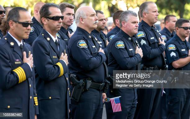Members of the Orange County Fire Authority and the Tustin Police Department put their hands over their hearts as they recite the Pledge of...