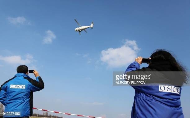Members of the Organization for Security and Cooperation in Europe Observer Mission Special Monitoring Mission in Ukraine watch the test flight of...