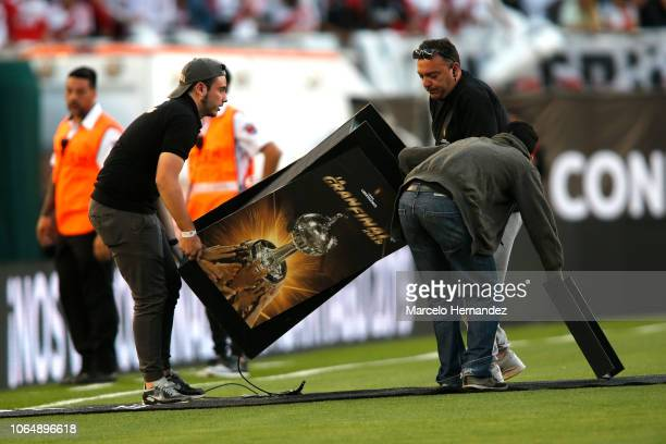 Members of the organization remove a signboard after the game is suspended before the second leg final match of Copa CONMEBOL Libertadores 2018...