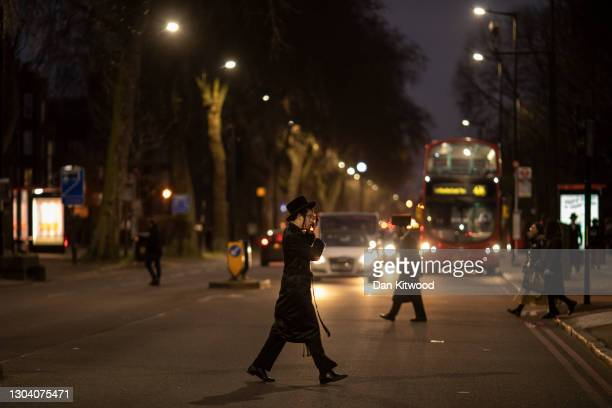 Members of the Orthodox Jewish community in Stamford Hill shortly after sunset, the start of Purim on February 25, 2021 in London, England. Last...