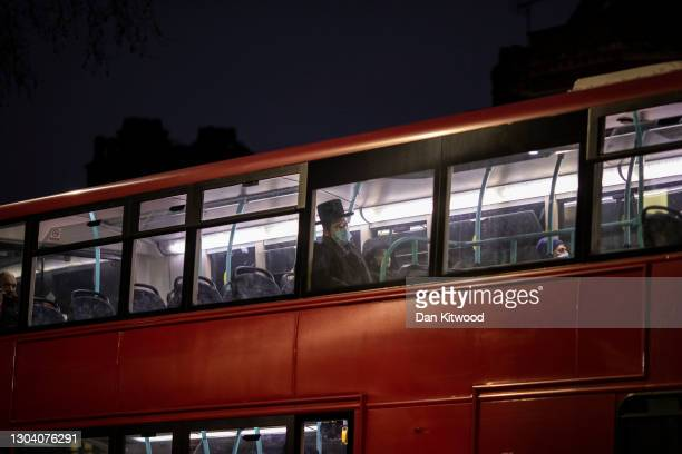 Members of the Orthodox Jewish community rides a bus in Stamford Hill shortly after sunset, the start of Purim on February 25, 2021 in London,...