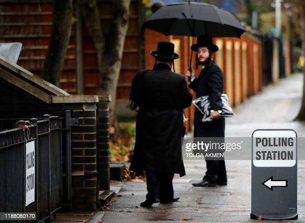 Members of the Orthodox Jewish community shelter from the rain beneath an umbrella as they walk past a polling station in north London as Britain...