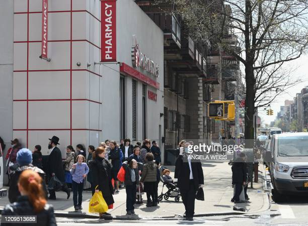 Members of the Orthodox Jewish community stand in line at a pharmacy on April 8 2020 in Brooklyn New York as the Passover holiday starts this evening...