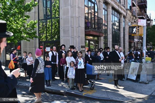 """Members of the Orthodox Jewish community watch as protesters walk through the Brooklyn borough on June 3 during a """"Breonna Taylor and Black Lives..."""