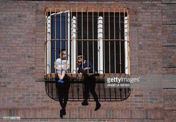 TOPSHOT Members of the Orthodox Jewish community watch from their windows as protesters walk through the Brooklyn borough on June 3 during a Breonna...