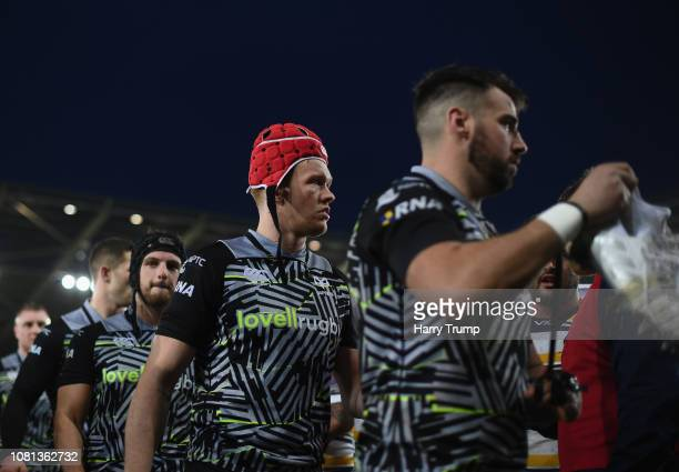 Members of the Ospreys side cut dejected figures during the Challenge Cup match between Ospreys and Worcester Warriors at Liberty Stadium on January...