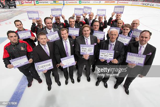 Members of the Ottawa Senators Hockey Operations department pose with 'I Fight For' signs on Hockey Fights Cancer night prior to a game against the...