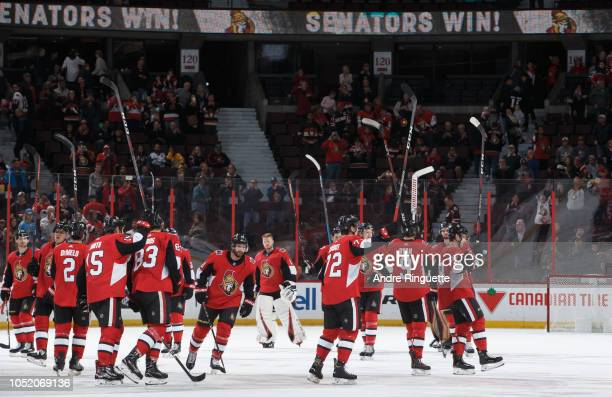 Members of the Ottawa Senators raise their sticks to celebrate their win over the Los Angeles Kings at Canadian Tire Centre on October 13 2018 in...