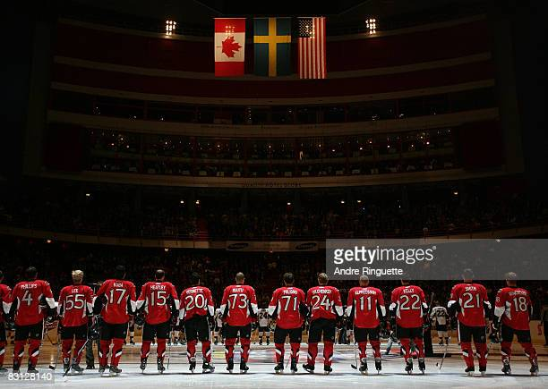 Members of the Ottawa Senators stand at the blue line during the singing of the national anthems prior to a game against the Pittsburgh Penguins at...
