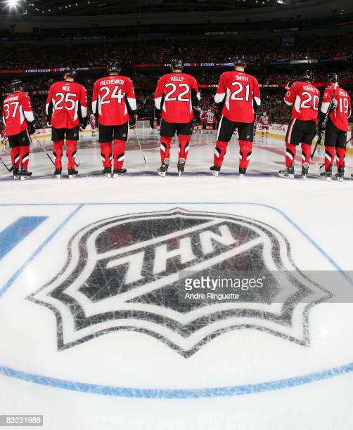 Members of the Ottawa Senators stand at the blue line in front of the NHL logo during the singing of the national anthems prior to a game against the...
