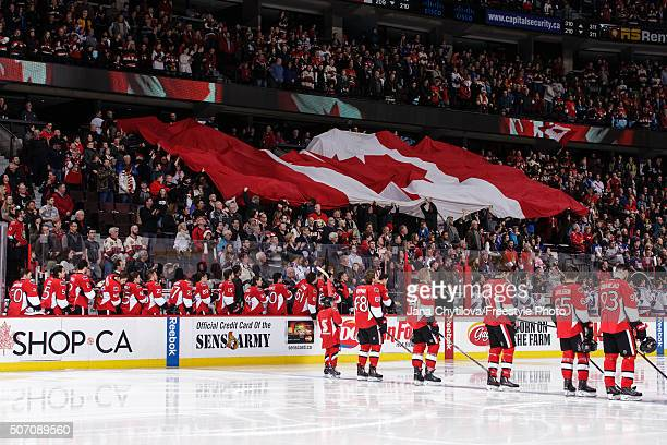 Members of the Ottawa Senators stand during the singing of the national anthems prior to an NHL game against the New York Rangers at Canadian Tire...