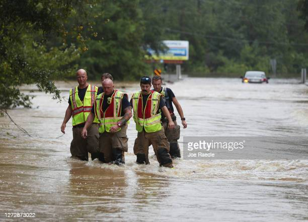 Members of the Pace Fire Rescue department wade through a flooded road after Hurricane Sally passed through the area on September 16 2020 in...