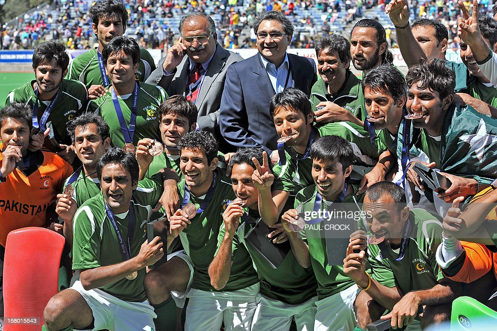 Members of the Pakistan hockey team celebrate as they hold their bronze medals after their match against India at the men's Hockey Champions Trophy tournament in Melbourne on December 9, 2012