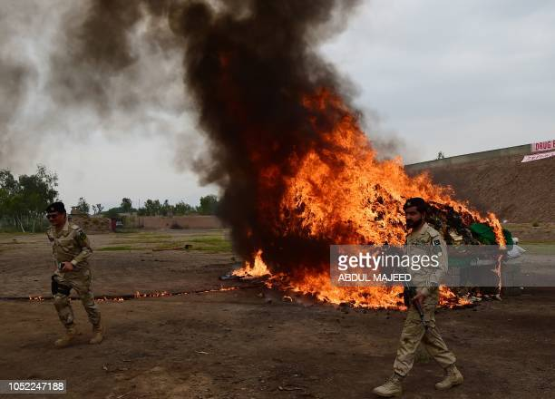 Members of the Pakistani AntiNarcotic Force walk past a pile of burning drugs and liquor during a ceremony at the Kacha Ghari army firing range on...