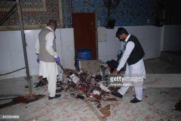 Members of the Pakistani bomb disposal team collect evidences from the site of a suicide attack at the 13th century old shrine of a Muslim saint in...