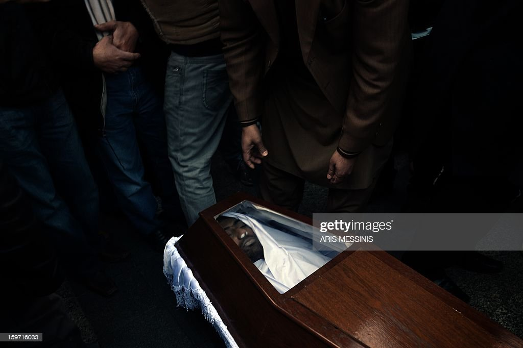 Members of the Pakistani community in Athens gather on January 19, 2013 around the coffin of a 27 years old Pakistani migrant victim of what appears to be a racism-fuelled crime. Hundreds of Greeks and other nationals marched peacefully against racism and fascism on January 19. Nearly 3,000 people joined the rally that was set up by municipalities, organisations, migrant communities and main opposition party radical leftists Syriza. This week, authorities arrested a 29-year-old firefighter and another Greek man aged 25 for the murder of the 27-year-old Pakistani migrant.