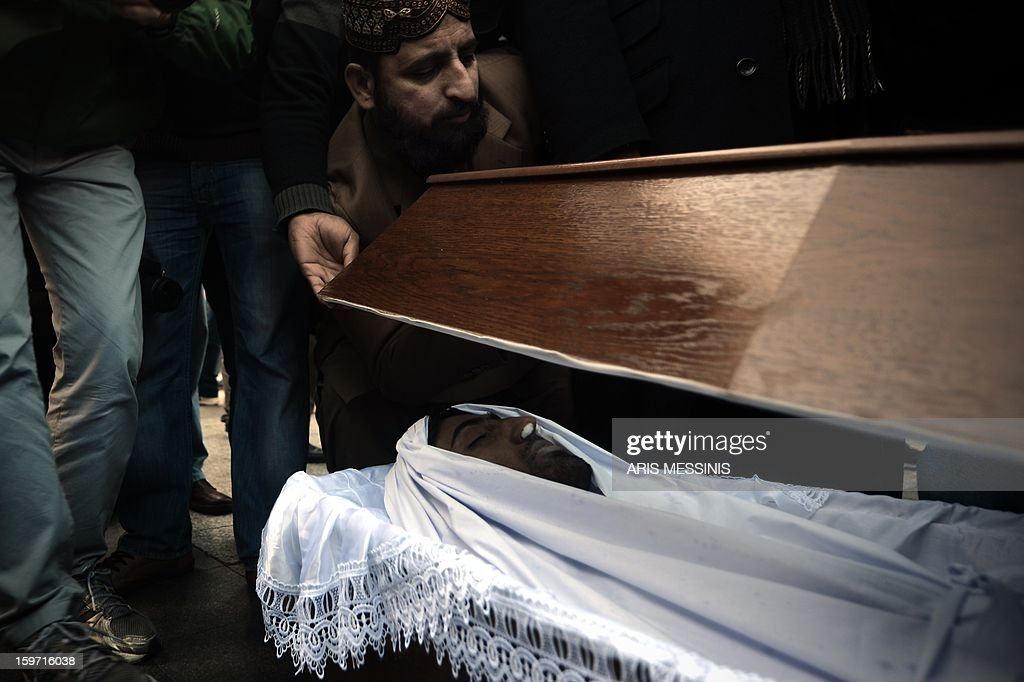Members of the Pakistani community in Athens gather on January 19, 2013 around the coffin of a 27 years old Pakistani migrant victim of what appears to be a racism-fuelled crime