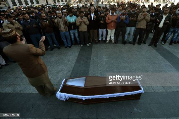 Members of the Pakistani community in Athens pray on January 19 2013 around the coffin of a 27 years old Pakistani migrant victim of what appears to...