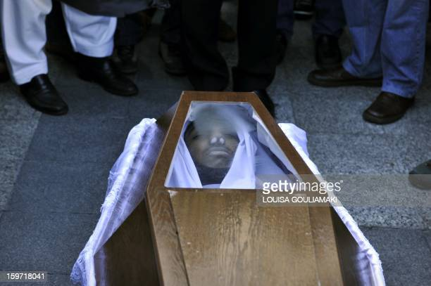 Members of the Pakistani community in Athens stand on January 19 2013 around the coffin of a 27 years old Pakistani migrant victim of what appears to...