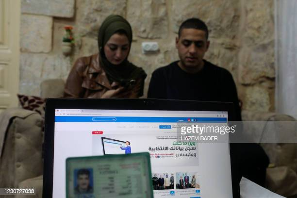 Members of the Palestinian Abu Shamsiyeh family register to vote through the Palestinian Elections Committee website, at home in the West Bank city...