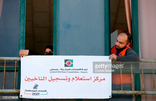 """Members of the Palestinian Central Elections Commission hang a sign reading in Arabic """"voter information and registration centre"""" in the West Bank..."""