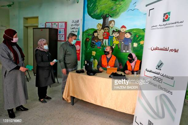 Members of the Palestinian Central Elections Commission register voters in the West Bank town of Hebron on February 10, 2021. - Rival Palestinian...