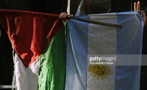 Members of the Palestinian community in Argentina hold flags during a demonstration against Israeli strikes in Gaza in front of Israel's Embassy in...