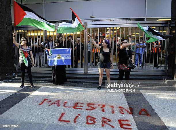 Members of the Palestinian community in Argentina wave flags during a demonstration against Israeli strikes in Gaza in front of Israel's Embassy in...