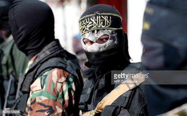 Members of the Palestinian Islamic Jihad Movement and masked militants attend the funeral of comrades killed in an Israeli operation to blow up a...