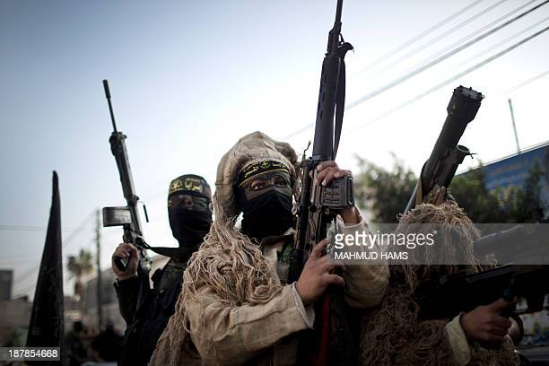 Members of the Palestinian Islamic Jihad movement parade with guns on November 13 2013 in the streets of Gaza City during an antiIsrael march as part...