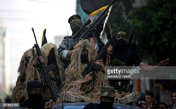 Members of the Palestinian Islamic Jihad movement parade with guns on November 13, 2013 in the streets of Gaza City during an anti-Israel march as...