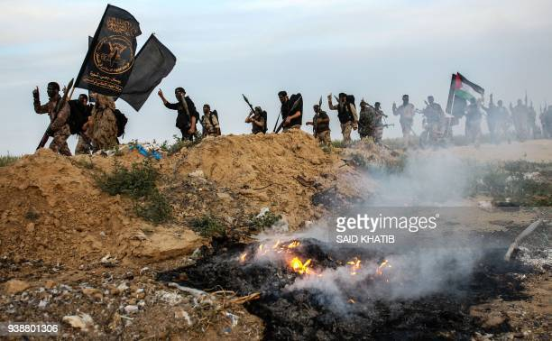 TOPSHOT Members of the Palestinian Islamic Jihad movement shout slogans as they march with firearms during a military drill in Khan Yunis in the...