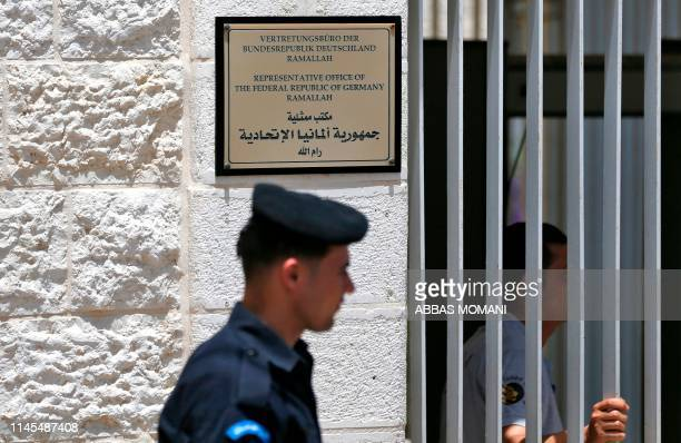 Members of the Palestinian police stand guard outside Germany's Representative Office in Ramallah in the West Bank on May 22 following the...