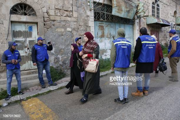 Members of the Palestinian Youth Against Settlements activists escort Palestinian pedestrians in the occupied West Bank town of Hebron on February 10...