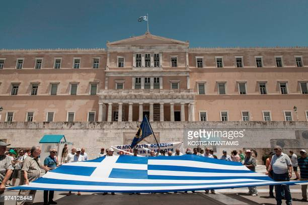 Members of the Panhellenic Federation of Retired Officers of Security Forces hold a big Greek flag in front of the Greek Parliament during a protest...