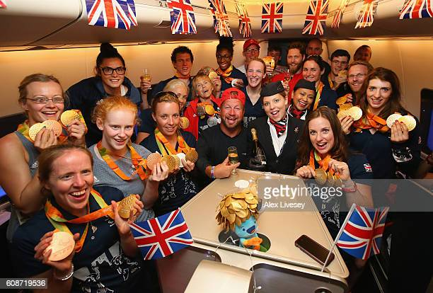 Members of the Paralympics GB Team show their medals as the British Airways cabin crew pour champagne prior to the flight back from Galeao Airport on...