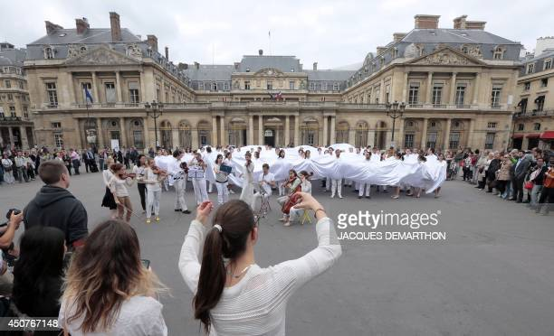 Members of the Paris Academy of Music perform on the PalaisRoyal square in Paris on June 17 2014 during a flashmob entitled 'Voile blanc sur l'opera'...