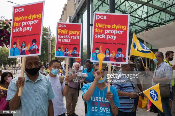 Members of the PCS trade union working for the outsourced contractor ISS stand on the picket line outside their workplace at the Department for...
