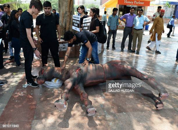 Members of the People for the Ethical Treatment of Animals animal rights organization hold placards as they stand near a dummy of an 'injured' horse...