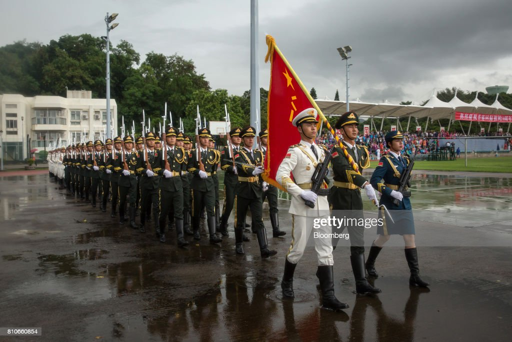 Members of the People's Liberation Army (PLA) march with a flag during a drill demonstration at an open day at the Ngong Suen Chau Barracks in Hong Kong, China, on Saturday, July 8, 2017. China's bid to display some soft power in Hong Kong-- with a visit by the country's first aircraft carrier -- has also showcased its heavy-handed approach to security. Photographer: Billy H.C. Kwok/Bloomberg via Getty Images