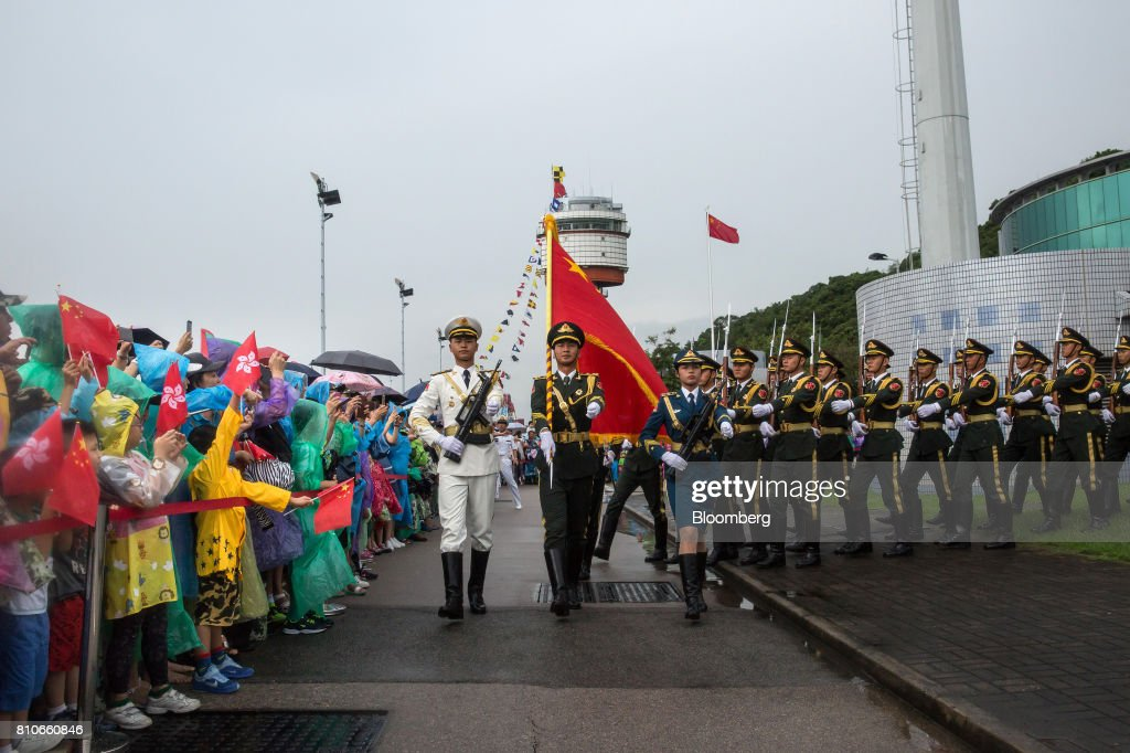 Members of the People's Liberation Army (PLA) march with a flag past visitors holding the flags of China and Hong Kong Special Administrative Region during a drill demonstration at an open day at the Ngong Suen Chau Barracks in Hong Kong, China, on Saturday, July 8, 2017. China's bid to display some soft power in Hong Kong-- with a visit by the country's first aircraft carrier -- has also showcased its heavy-handed approach to security. Photographer: Billy H.C. Kwok/Bloomberg via Getty Images