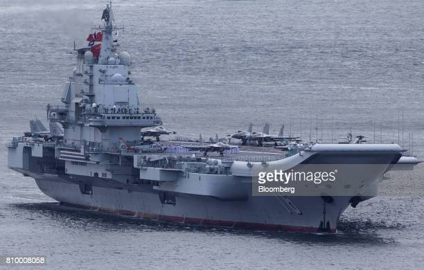 Members of the People's Liberation Army Navy stand on the Liaoning aircraft carrier as it sails into Hong Kong china on Friday July 7 2017 The...